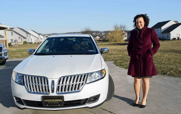 Jill Anderson stands beside her hybrid car, a Lincoln MKZ, on Wednesday, April 3, 2013.