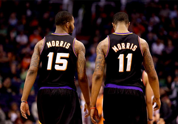 Phoenix Suns forwards Marcus (15) and Markieff Morris (11), who are twins, walk down the court together.