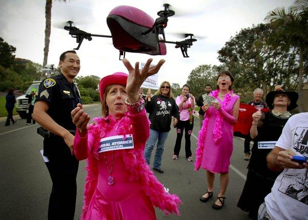 San Diego Police Sgt. Dan Sayasane looks on in La Jolla as a small drone lands in the hand of anti-drone protester Medea Benjamin.