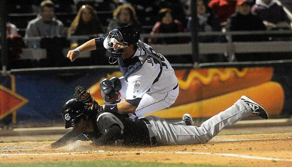 Syracuse Chiefs' Mike Costanzo slides under the tag from Lehigh Valley IronPigs' catcher Tommy Joseph at Coca-Cola Park in Allentown Friday night.