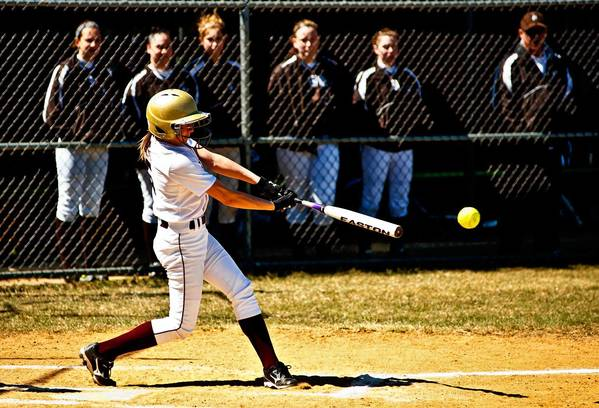 Whitehall's bats were hot Saturday, Rachel Spanitz (5) gets a base hit as the Rough Riders watch.