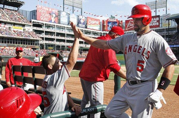 Angels first baseman Albert Pujols is greeted by Peter Bourjos as he returns to the dugout following a home run in the sixth inning Saturday afternoon in Texas.