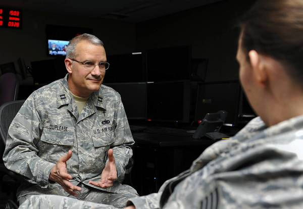 Capt. Robert DuPlease, an Air Force chaplain, counsels an airman at the operations center of the 497th Intelligence, Surveillance and Reconnaissance Group at Langley Air Force Base in Hampton. The Air Force has embedded DuPlease and a clinical psychologist with the group, and at similar units.