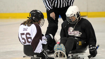 Christa Diaz and Amy Bradley battle for control of the puck Saturday in a sled hockey game.