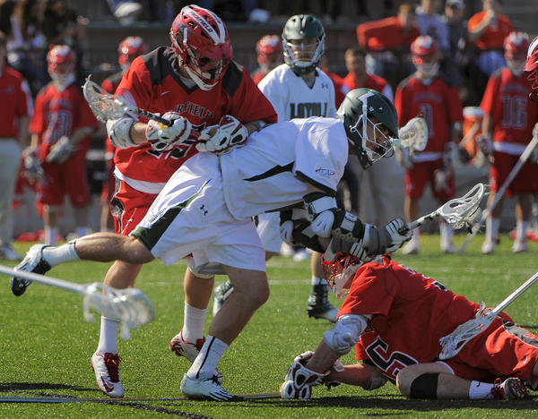 Fairfield midfielder TJ Neubauer, left and defender Greg Perraut, right attempt to sandwich Loyola attack Mike Sawyer, who still winds up scoring an across-the-body shot.