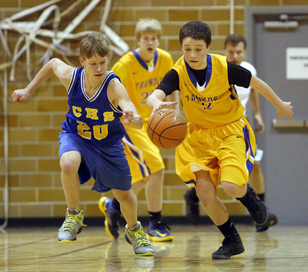 Conner Chamberlain, of the Aberdeen Thunder, right and Caleb DeKam, of the Castlewood Warriors, left, go after the ball during their bracket 7-1 game in the Aberdeen Family YMCA Interstate Basketball Tournament Saturday at the Washington Street Gym. photo by john davis taken 4/6/2013