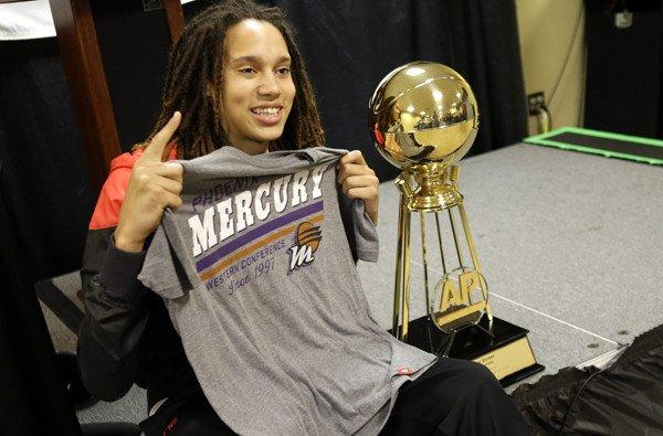 Brttney Griner holds up a Phoenix Mercury T-shirt as she poses next to the Associated Press Player of the Year Trophy during a news conference.