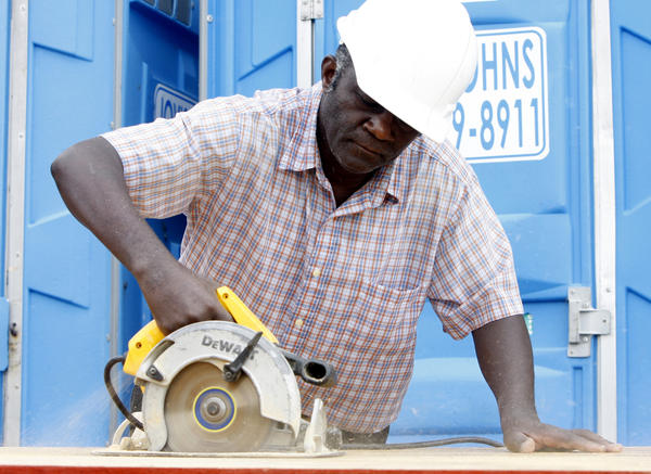 This 2010 file photo shows Elyse Gasigwa sawing plywood while working on his Habitat for Humanity house in Mishawaka. His family moved from Rwanda to St. Joseph County in 2007.