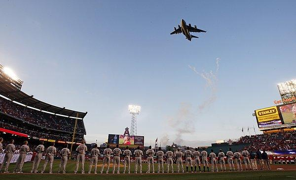 An Air Force C-17 Globemaster military transport plane flies over Angels Stadium in Anaheim on opening day in 2010.