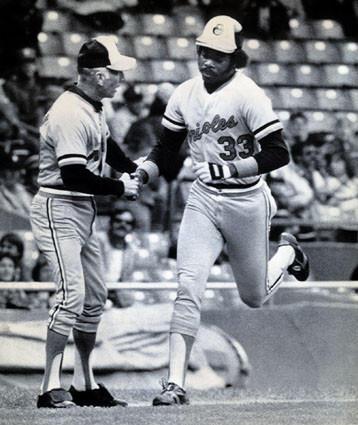 Eddie Murray is congratulated by Cal Ripken Sr. on a home run.
