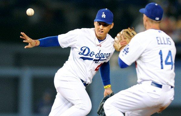 Dodgers shortstop Luis Cruz tosses the ball to second baseman Mark Ellis to begin a double play against the Giants.