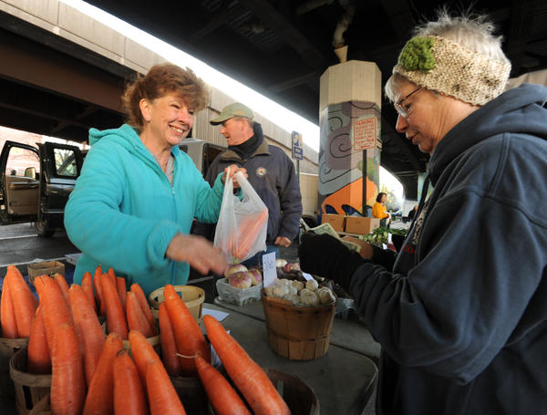Lisa Reynolds, left, with Marshall Farms, sells produce to Sherry Trabert on the first day of the Farmers' Market under the JFX. In the background center is John Marshall Jr.