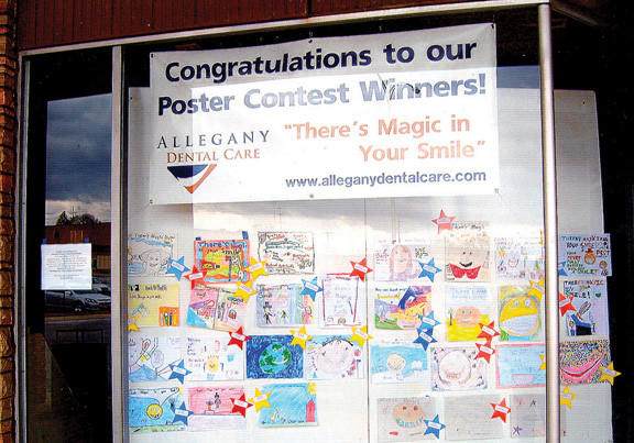 Posters on display in a store window at Long Meadow Shopping Center are entries in Allegany Dental Cares annual poster contest for local elementary school second-graders. The theme of the contest is Theres Magic in Your Smile.