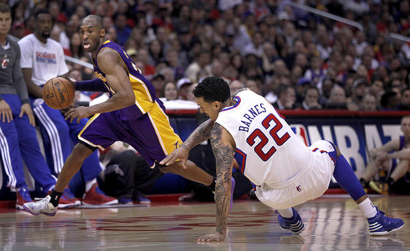 Clippers forward Matt Barnes loses his balance as Lakers guard Kobe Bryant drives around him in the second half Sunday afternoon.