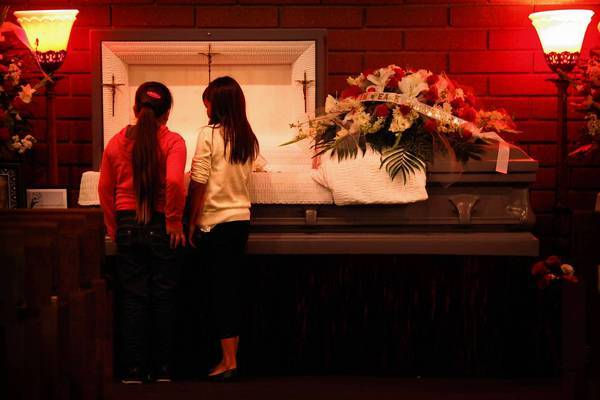 Cecilia Renteria, right, looks into her father's coffin with a friend on Friday.