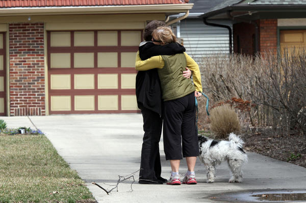 Cathy Tokarski, right, of Oak Park, hugs a relative in the driveway of Anne Smedinghoff's family home in River Forest. Anne Smedinghoff, 25, a diplomat from River Forest was among five Americans killed Saturday in an explosion in Afghanistan, according to her family and the U.S. State Department. White ribbons and American flags line the 800 block of Williams St. where her family lives.