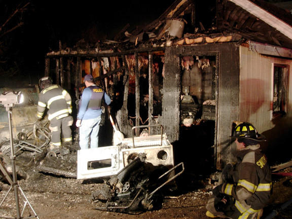 Deputy State Fire Marshal Ed Ernst, center, looks at the scene of a fire on Paden Avenue in Smithsburg Sunday night.