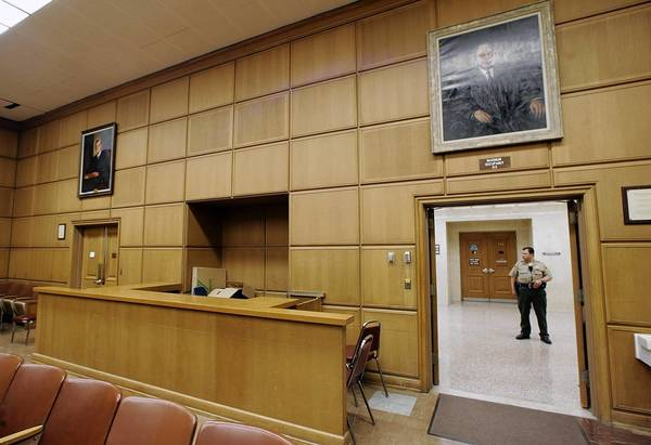 A Los Angeles County court bailiff stands in an empty hallway in the downtown Los Angeles courthouse.