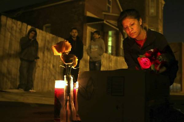 Ruby Perdomo places flowers at the site of a fatal shooting of a 14-year-old boy Sunday on the West Side.