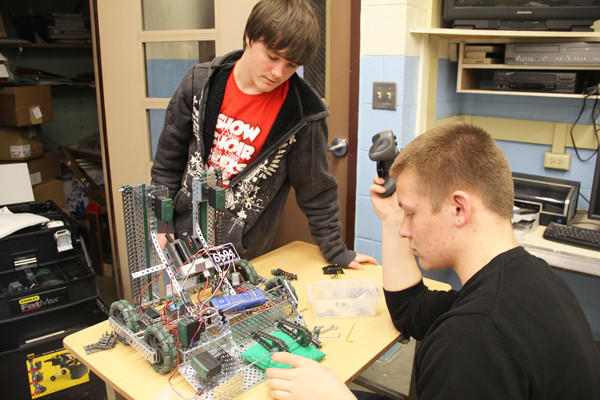 Logan Lane, far right, works on the Geek Squad's robot during his sophomore technology class with teammate Devon Poppen.