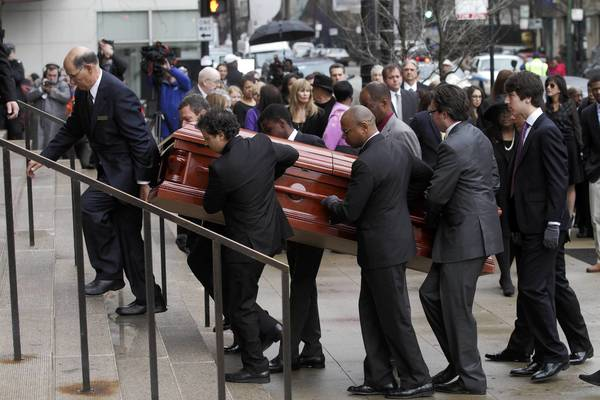 Pallbearers carry Roger Ebert's casket into Holy Name Cathedral in Chicago for his funeral.