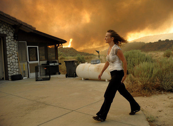 An unidentified woman watches as flames approach her home from a fast-moving wildfire near Palmdale.