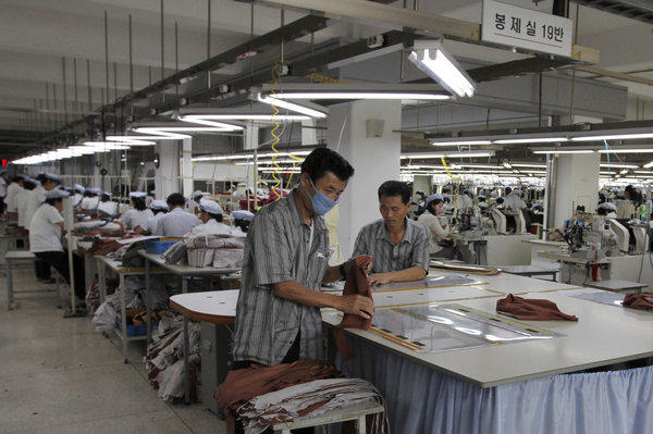 In this file photo, two North Koreans working for ShinWon, a South Korean clothing maker, prepare garments for production at a factory in Kaesong, North Korea.