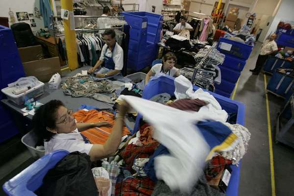 Workers sort clothes at Goodwill in Hollywood. Other nonprofits contend the the charity is trying to monopolize used-clothing donations.