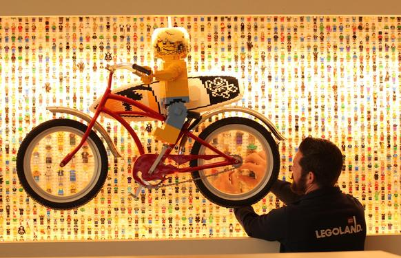 Five thousand miniature Lego people have been mounted as wall decoration at the new Legoland Hotel in Carlsbad. The bicycle travels along the wall, its wheels acting as magnifying glasses for a better look at
