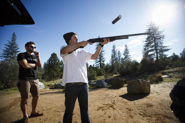 Josh Capfer, 19, shoots his shotgun as his friend, Taylor Pearson, 21, looks on at a public shooting range in Redding.