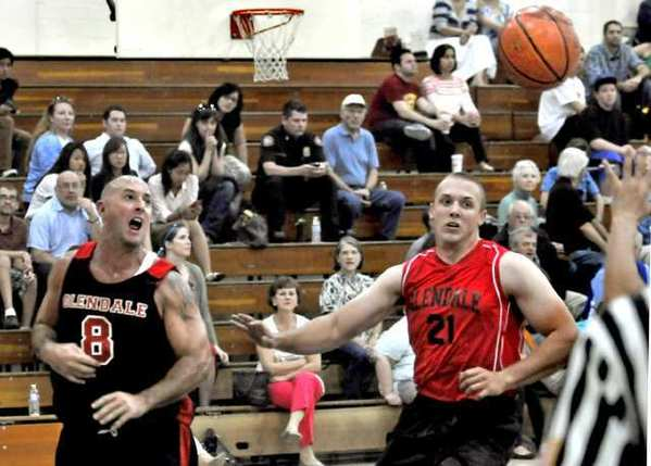 Firefighter Scott McMahon (8) and Police's Scott Wessel (21) play during the annual Hoop Heroes Basketball Championship Game at Glendale High School.