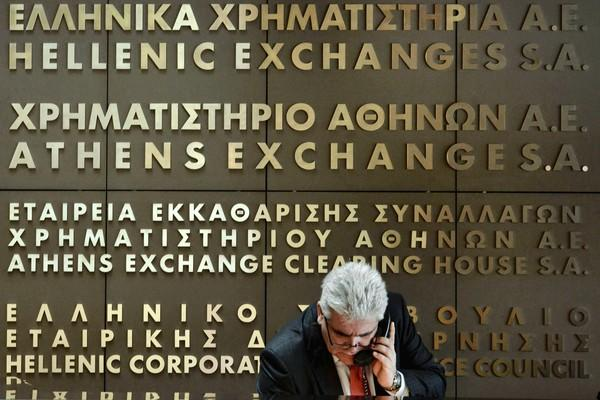 Investors dumped shares of the National Bank of Greece and Eurobank after the institutions confirmed that their merger was on hold. Above, an employee at the Athens stock exchange.
