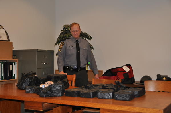 Trooper Michael Volk unpacks the duffel bag that was filled with bricks of heroin.
