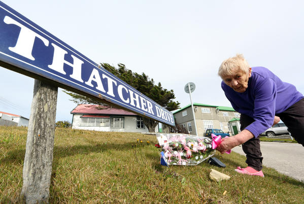 A woman in Port Stanley, Falkland Islands, places flowers to honor the memory of former British Prime Minister Margaret Thatcher.