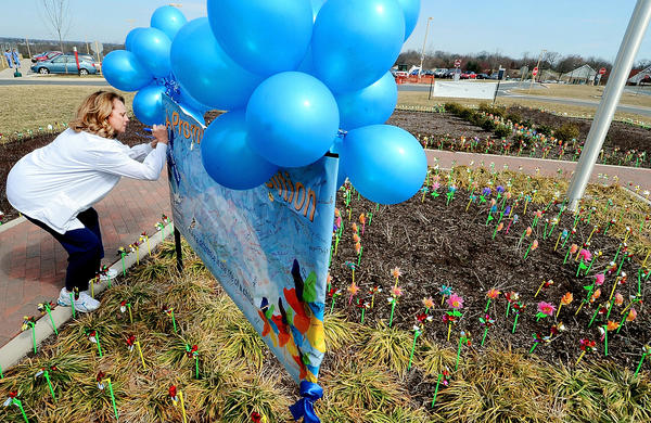Dena Green, manager of labor and delivery at Meritus Medical Center, signs a banner amidst pinwheels placed outside the hospital Monday in observance of Child Abuse Prevention and Sexual Assault Awareness Month.