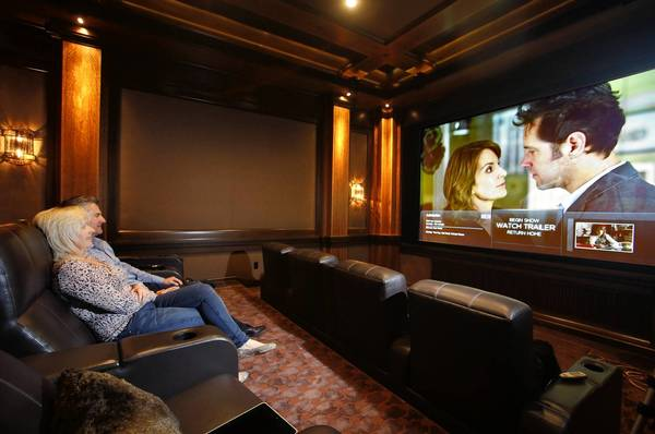 A San Diego-area firm enables the wealthy to show in their home theaters movies that are still at the multiplex.