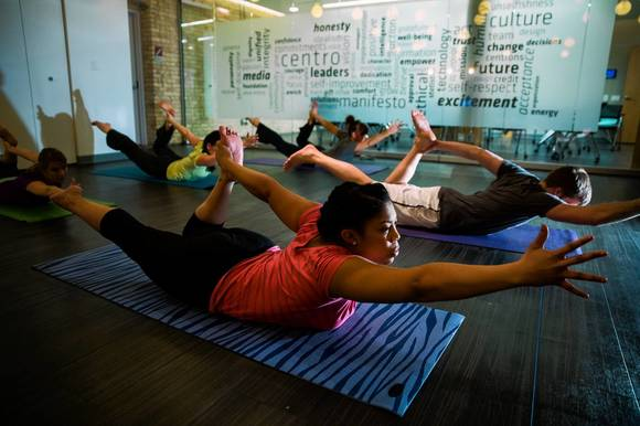 Krystle Singletary, 28, front, joins other employees taking a yoga class during their lunch hour at the Centro advertising agency in Chicago.
