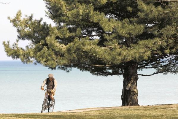 A bicyclist passes along a lakefront path Monday in Winnetka as the Chicago region enjoys some spring warmth. By Friday it could be snowing, National Weather Service meteorologists say.
