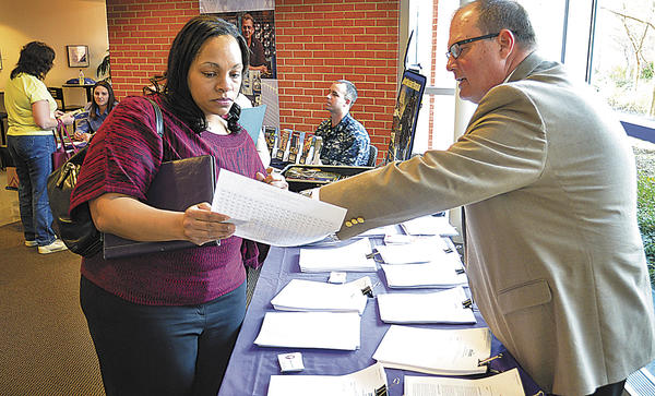 DeAnna Atkinson of Hagerstown looks over a wage scale Monday with Mark Smith, personnel officer with the Washington County Department of Social Services, at a job fair at the University System of Maryland at Hagerstown.