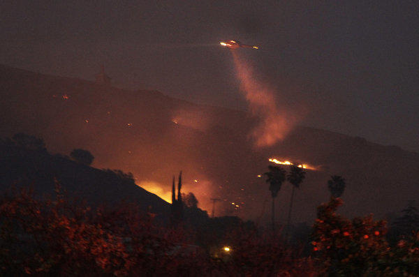 A Ventura County Fire Department helicopter drops water onto a hot spot as night falls in Fillmore.