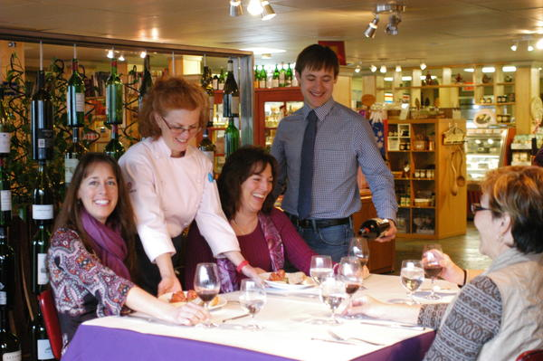 Leilani Durbin (left) and Cindy Vermeesch (also seated) enjoyed wine and hors d'oeuvres at Esperance Saturday during a wine tasting event to benefit Keep Charlevoix Beautiful. Similar tasting events are planned at the wine shop in Charlevoix each Saturday through May 25. Also pictured is store owner Suzanne Acharya and employee Aaron Hagen.