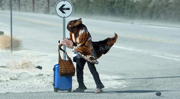 A woman tries to keep her balance amid gusty winds and blowing sand while waiting for her ride after arriving in Palm Springs by bus.