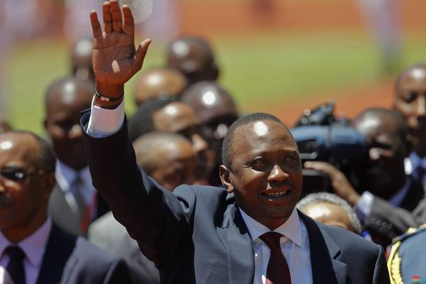 Kenya's Uhuru Kenyatta waves as he arrives at his presidential inauguration ceremony on the outskirts of Nairobi.