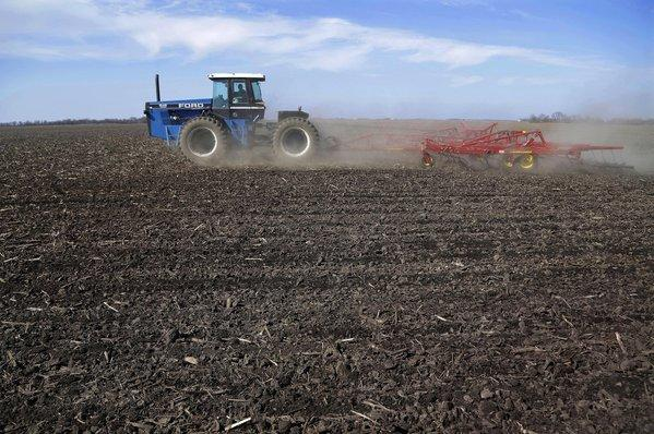 A central Illinois corn and soybean farmer cultivates his field in preparation for spring planting.