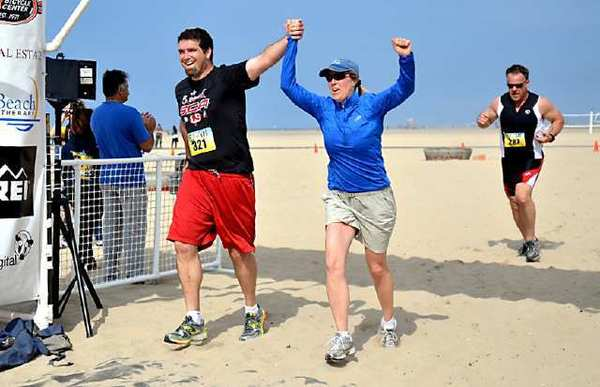 Brent Killey, left, of Huntington Beach, and wife Debbie Killey, cross the finish line together while holding hands at the Huntington Beach Triathlon and 5K Run/Walk at Huntington State Beach on Saturday.