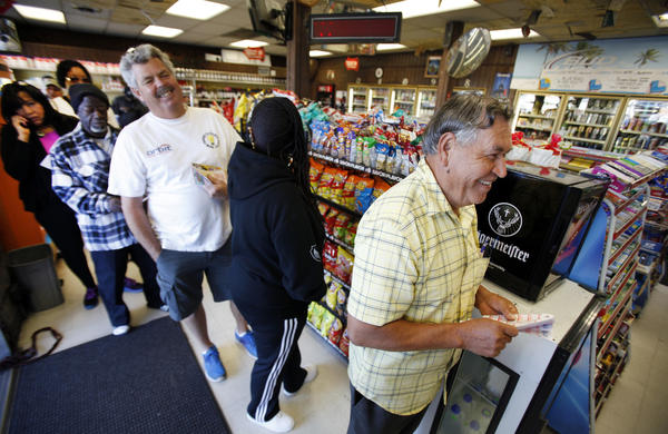 Rafael Moreno picks his lucky numbers as people form a line for Powerball tickets at Bluebird Liquor in Hawthorne.