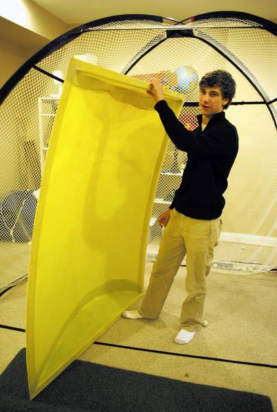 Jonny Cohen, 17, stands beside the latest prototype of GreenShields, a wing-shaped device to decrease drag and increase fuel efficiency for school buses.