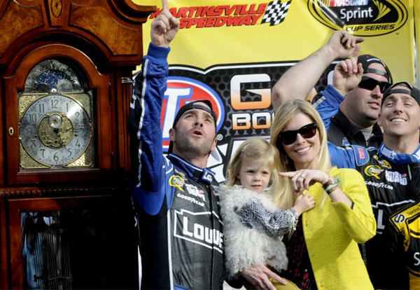 Jimmie Johnson, left, celebrates winning the STP 500 Sprint Cup series auto race with his wife, Chandra, and daughter, Genevieve.