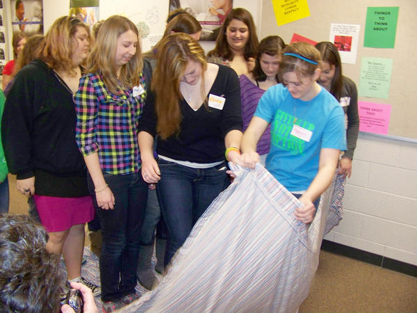 Area 9th and 10th grade students are trying to turn a sheet over while standing on it. This was one of the activities used to introduce girls to engineering careers sponsored by the Charlevoix-Emmet Intermediate School District and ferris State University