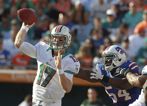 Dolphins quarterback Ryan Tannehill passes the ball as the Bills' Kyle Moore applies pressure during a game last season.